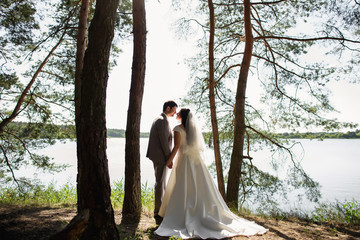 Bride and groom holding hands near lake in forest at wedding day