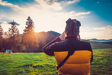 Nature photographer tourist with camera taking a photo in the mountains. Dreamy sunset landscape, spring green meadow and mountain top in the bsckground. Back view. Beautiful nature landscape. Travel