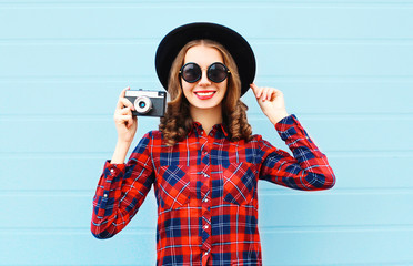 Fashion pretty young smiling woman and retro camera wearing a bl