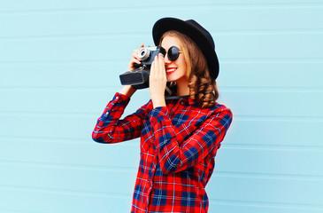 Fashion pretty young smiling woman with retro camera wearing bla