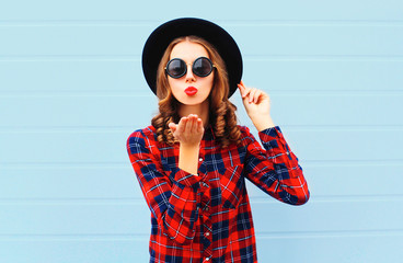 Fashion portrait woman blowing red lips sends air kiss wearing a