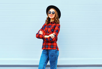 Fashion pretty young smiling woman wearing a black hat, red chec