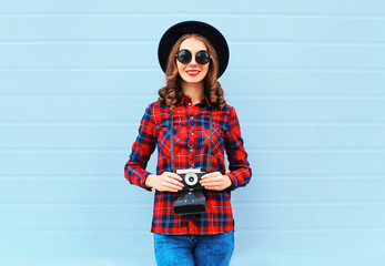 Fashion pretty young smiling woman holds retro camera wearing bl