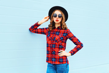 Fashion young woman model wearing black hat, red checkered shirt