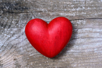 Red hart on wooden background - love symbol
