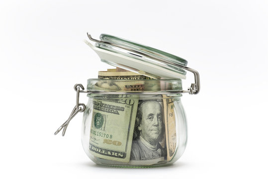 Dollar bills in glass jar isolated on white background. Saving money concept.