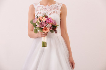 Bride holding wedding bouquet on white background, closeup