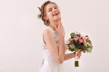 Young beautiful bride holding wedding bouquet on white background
