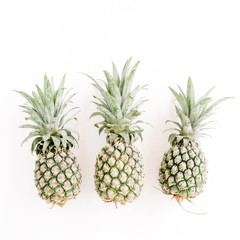 Three pineapples on white background. Flat lay, top view