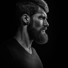 Black and white close-up portrait of young handsome bearded man