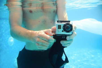 Young man with camera taking pictuser underwater