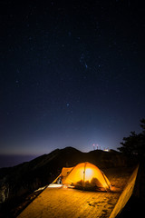The camping with stars on the top of the mountain.