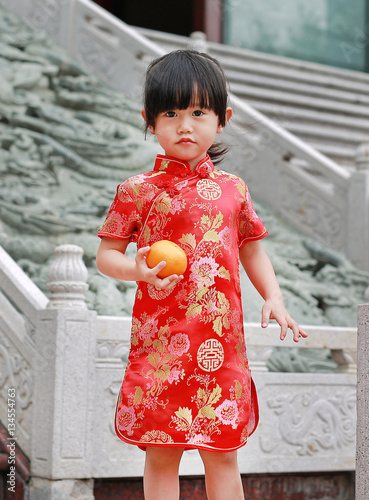 78bf929787d3d Cute asian kid girl in Red Traditional Chinese dress with holding sacred  Orange at chinese temple in bangkok thailand, Chinese new year concept.