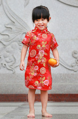 Cute asian kid girl in Red Traditional Chinese dress with holding sacred Orange at chinese temple in bangkok thailand, Chinese new year concept.