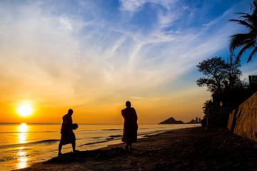 Buddhist monks walk collecting alms, morning beach.