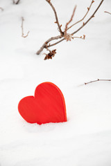 Red heart in the snow on a winter background. St. Valentine's Day