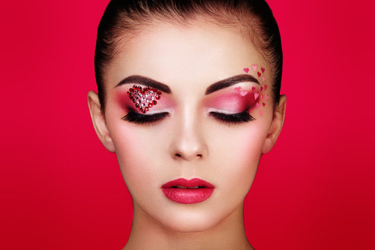 Face of beautiful woman with holiday makeup heart. Valentine's day make-up. Lips in pink lipstick. Makeup detail. Face of girl on a red background