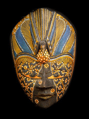 Wooden carved Malaysian tribal face mask on a black background