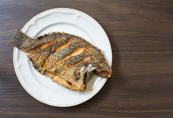 Fried fish in white dish on dark brown wooden plate thai food