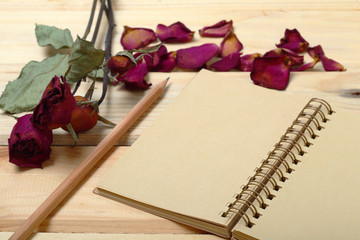 Empty notebook and dry roses with pencil on old wood