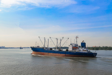 Logistic concept,Cargo ship was sailing out of the port within the river. To the sea And next to the port of destination.