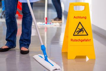 Warnschild vor arbeitender Putzkolonne