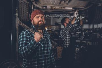 Two bearded mechanics in a garage.