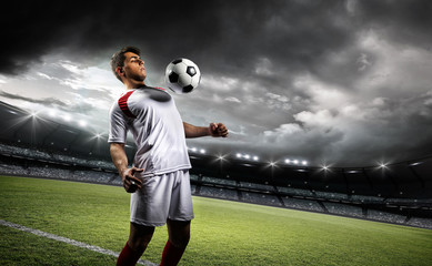 Fototapete - Football player withstand a ball with his chest in the stadium