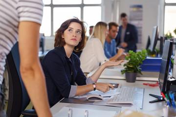 mitarbeiterin zeigt genervt auf ihren computer