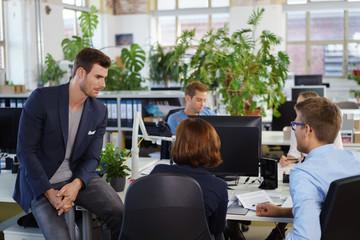 team im büro unterhält sich am schreibtisch