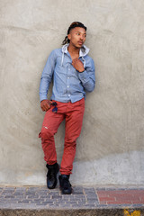 cool african guy leaning against wall
