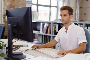mann arbeitet konzentriert am computer