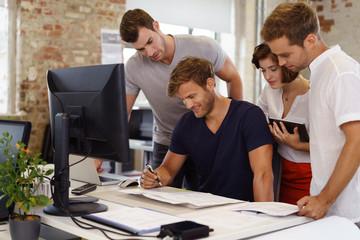 junges team im büro schaut gemeinsam auf unterlagen