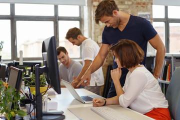mitarbeiter unterhalten sich am arbeitsplatz und schauen auf laptop
