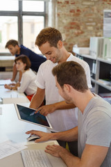 kollegen im büro schauen gemeinsam auf ein tablet