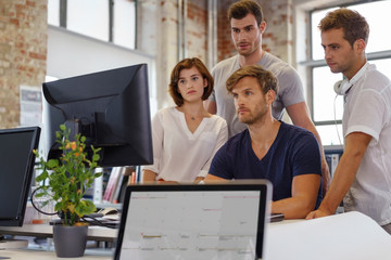 team schaut mit ernstem gesicht auf den computer