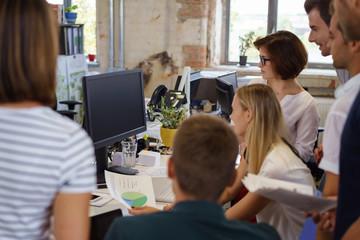 mitarbeiter schauen gemeinsam auf computer
