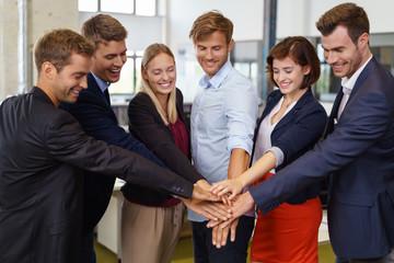 motiviertes team im büro hält die hände zusammen