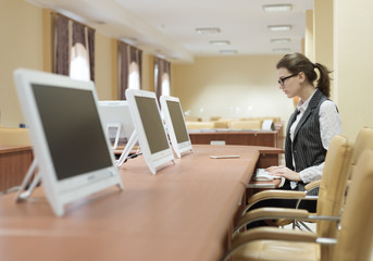 Businesswoman wearing glasses working with a desktop computer at