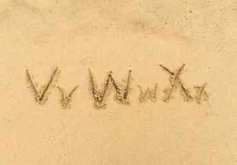 alphabet letters handwritten in sand on beach