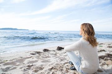 femme en hiver assise sur la plage