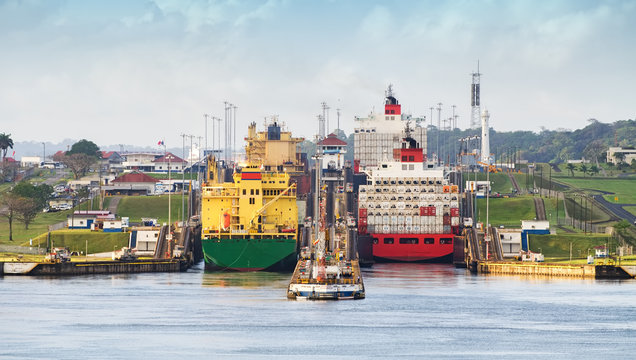 panama canal,  a cargo ship entering the miraflores locks in the