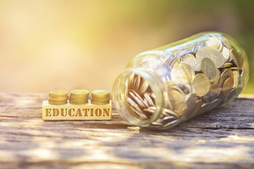 EDUCATION WORD Golden coin stacked with wooden bar on shallow DOF