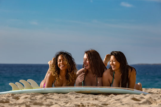 Three surfer girls lying on a surfing board having fun at a beach in sand. Blue ocean background