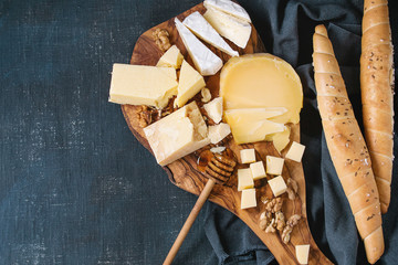 Cheese plate. Assortment of cheese with walnuts, honey and bread on olive wood serving board with textile over dark blue canvas as background. Top view with space.