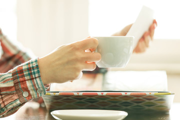 Woman Looking at Photo Album and Having a Cup of Coffee. Close u