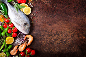 Fresh fish, shrimps with herbs, spices and vegetables on dark vintage background. Healthy food, diet or cooking concept. Free space for your background