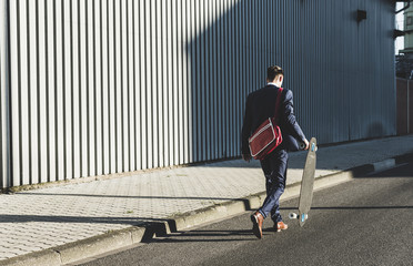 Young businessman walking with skateboard on the street