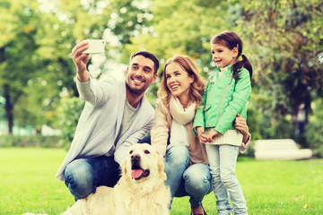 happy family with dog taking selfie by smartphone