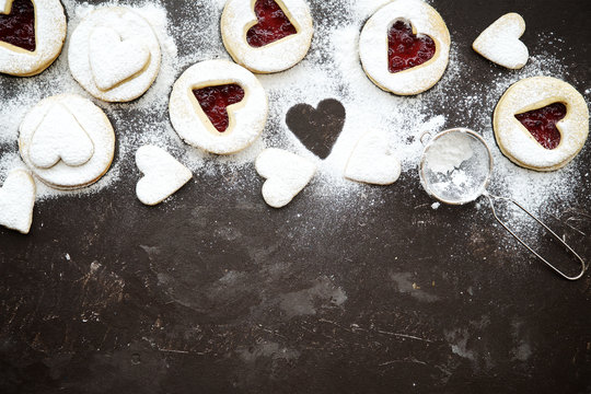 Homemade heart shaped linzer cookies with jam on wooden texture background, top view, copy space